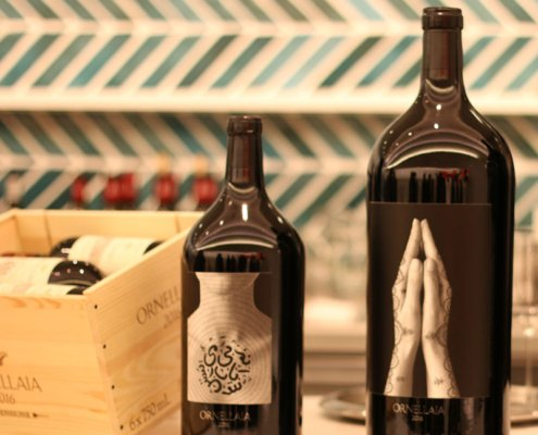 Two ornate large-format bottles of Ornellaia red wine.