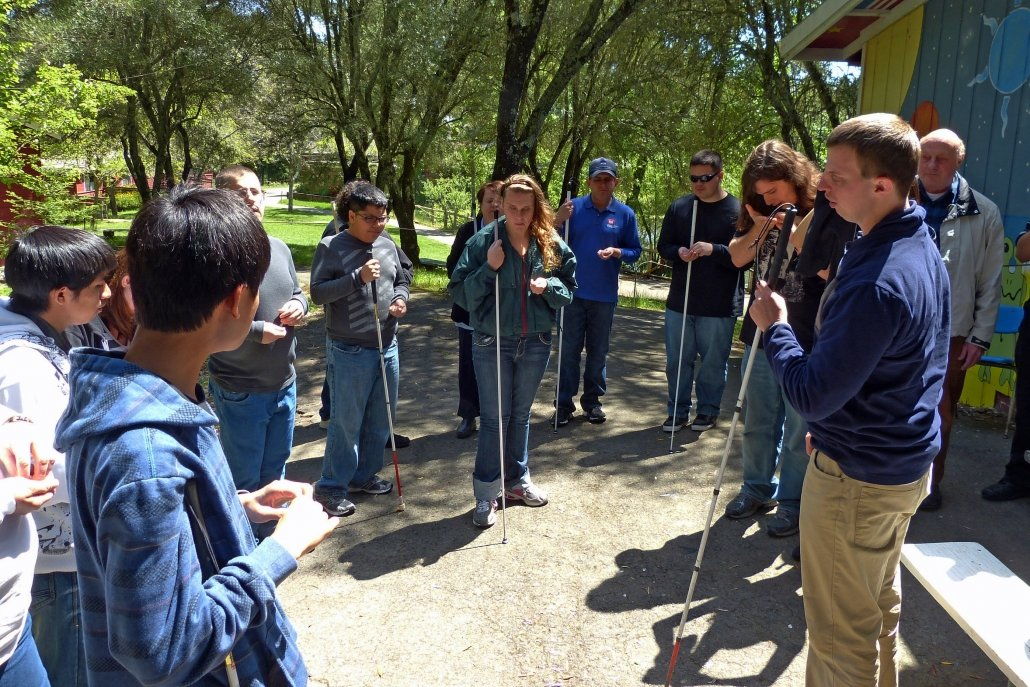 Blind people standing in a circle in a park, talking and holding their white canes.